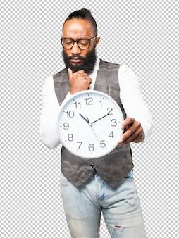 Coole zwarte man met een klok