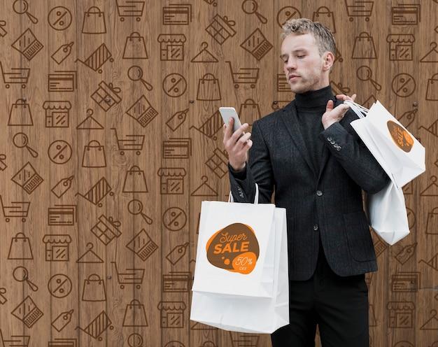 Copia espacio hombre de compras comprobando teléfono