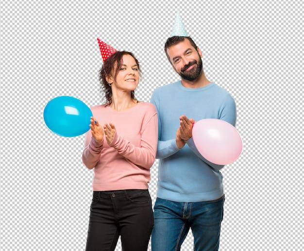 Coppia con palloncini e cappelli di compleanno che applaudono dopo la presentazione in una conferenza