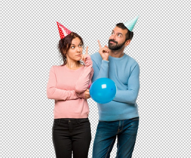 Coppia con palloncini e cappelli di compleanno che punta con il dito una grande idea e guardando in alto