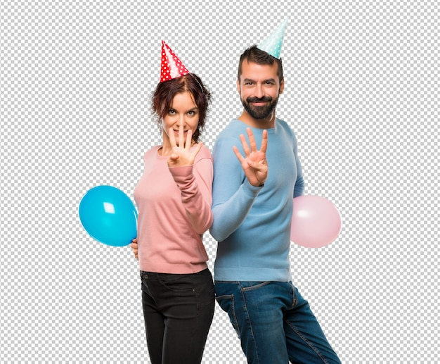 Coppia con palloncini e cappelli di compleanno felici e contando quattro con le dita