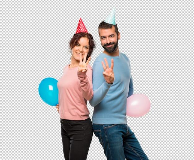 Coppia con palloncini e cappelli di compleanno felici e contando tre con le dita
