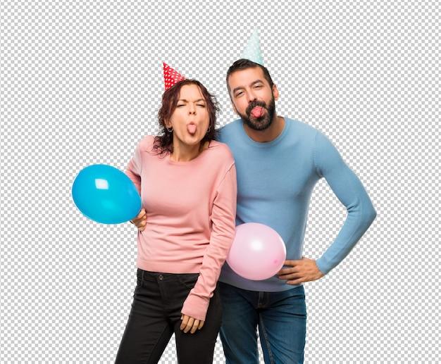 Coppia con palloncini e cappelli di compleanno mostrando la lingua alla fotocamera con sguardo divertente