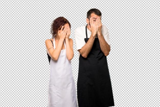 Coppia di cuochi che coprono gli occhi con le mani e guardano attraverso le dita