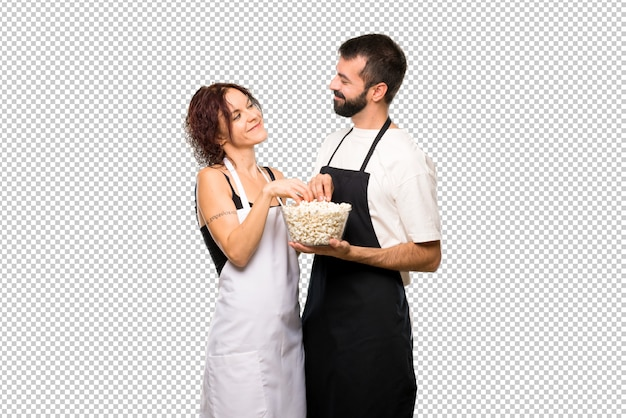 Coppia di cuochi che mangiano popcorn