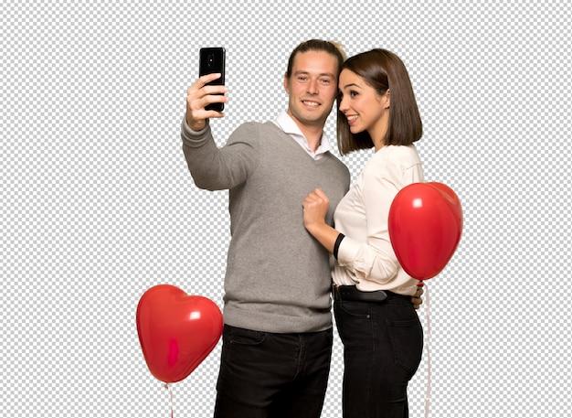 Coppia in san valentino felice e indicando il cellulare