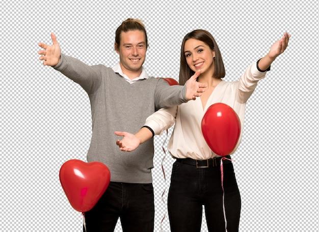 Coppia nel giorno di san valentino che presenta e invita a venire con la mano