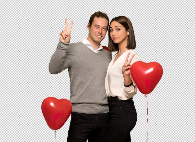 Coppia nel giorno di san valentino sorridendo e mostrando il segno della vittoria con entrambe le mani