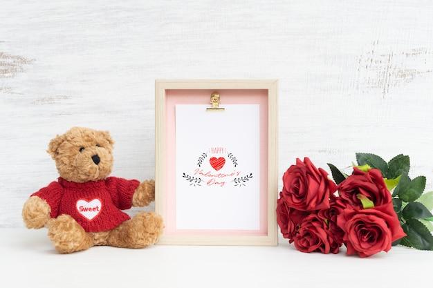 Cornice e simpatico orso con bouquet di rose rosse mockup