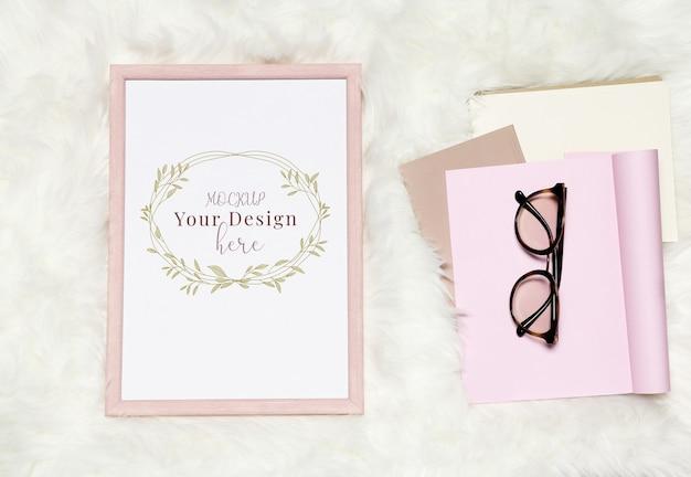 Cornice per foto su sfondo bianco simile a pelliccia con una pila di taccuini e occhiali