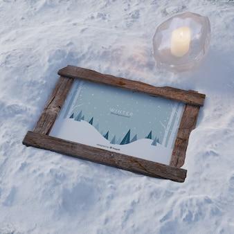 Cornice sulla neve con candela congelata