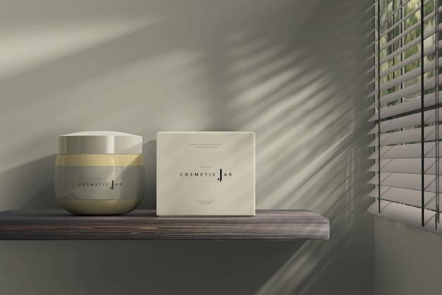 Cosmetische pot en doosmodel op plank naast raam