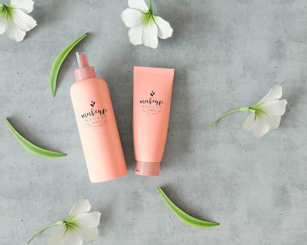 Cosmetische producten op cementoppervlak met bloemen