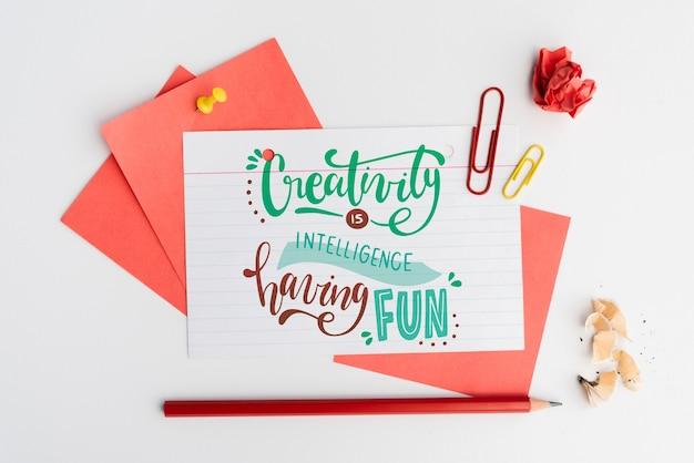 Creativiteit is intelligentie met pleziercitaat op wit papier met schrijfwaren