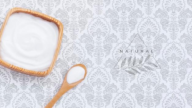 Crema de mantequilla corporal sobre maqueta de fondo liso