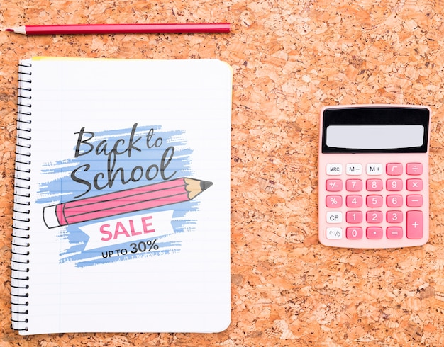 Cuaderno con lápiz junto a maqueta de calculadora.