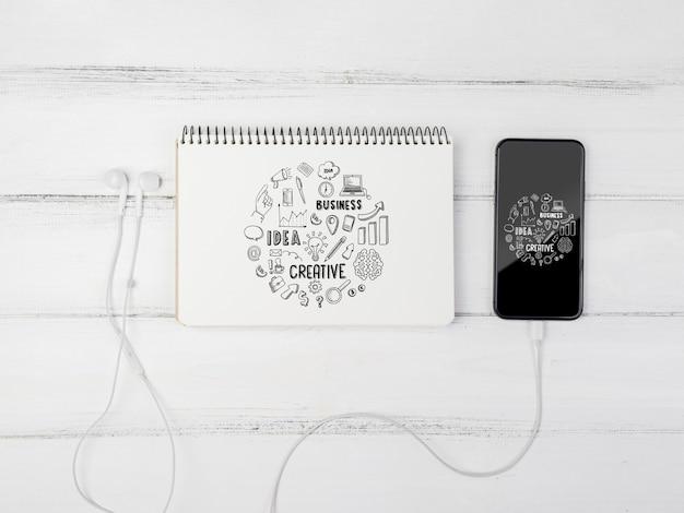 Cuaderno de maquetas con teléfono al lado