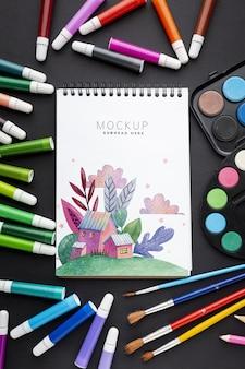 Cuaderno con marco de marcadores y pinceles