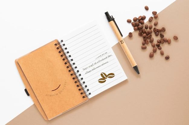 Cuaderno plano y granos de café.