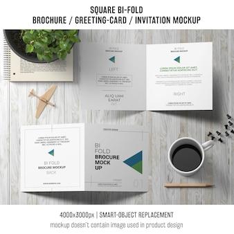 Cuadrado bi-fold folleto o tarjeta de felicitación maqueta en la mesa de madera