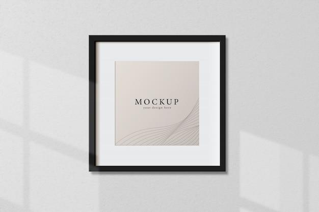 Cuadro de marco negro cuadrado vacío mínimo maqueta colgando sobre fondo de pared blanca con ventana de luz y sombra. aislar ilustración vectorial.