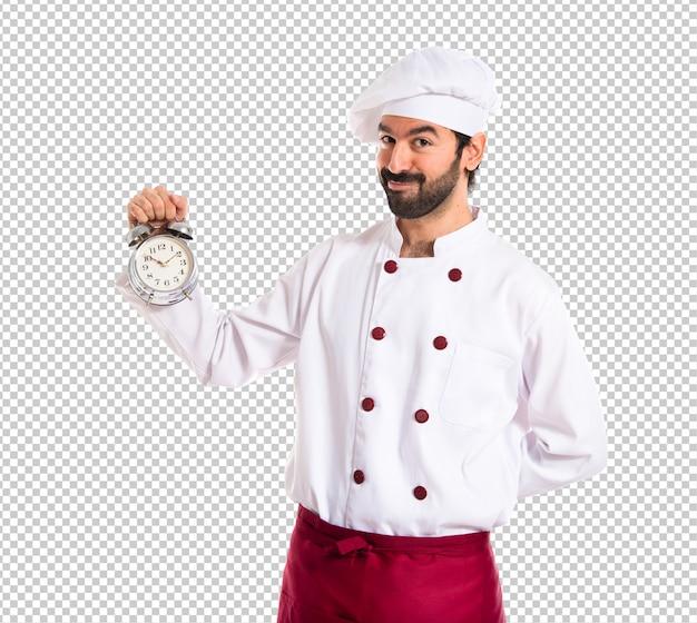 Cuoco unico che tiene un orologio sopra priorità bassa bianca