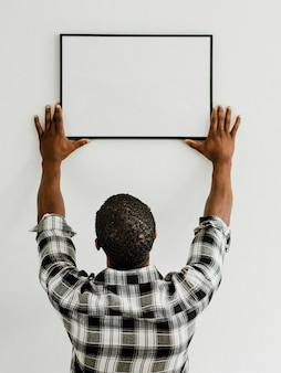 Curador colgando maqueta de marco de arte en la pared