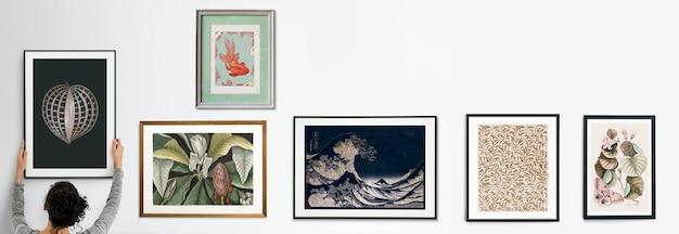 Curator hangende framemodellen aan de witte muur