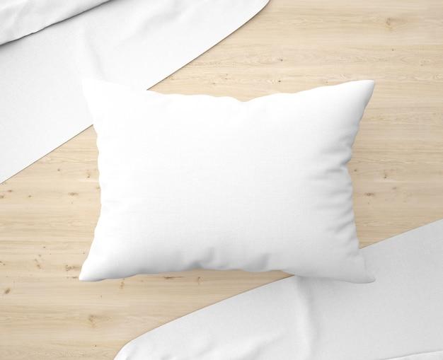 Cuscino bianco con lenzuola sul pavimento