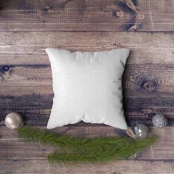 Cuscino su un tavolo di legno circondato da palline, pini e abeti