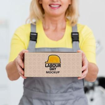 Dag van de arbeid mock-up box gehouden door vrouw
