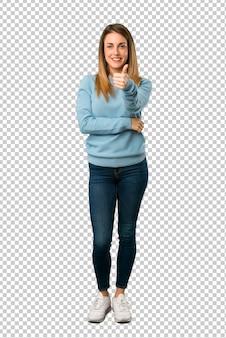 De blondevrouw met blauw overhemd die duimen geeft omhoog gebaar omdat iets goed is gebeurd