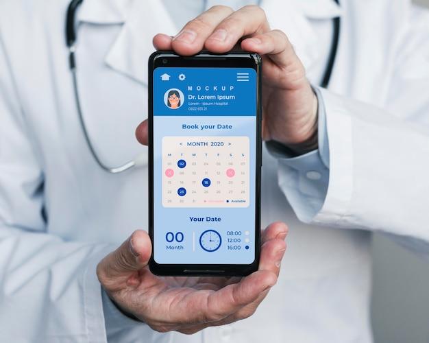 De hulplijn van de arts op mobiele telefoon die door arts wordt gehouden