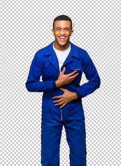 De jonge mens die van de afro amerikaanse arbeider een partij glimlachen terwijl het zetten van handen op borst