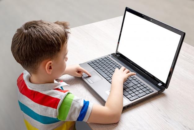De jongen gebruikt een laptop computermodel