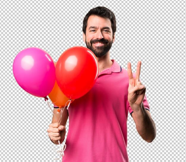 De knappe ballons van de jonge mensenholding en het tellen van twee