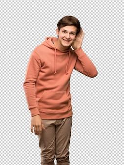De mens die van de tiener met sweatshirt aan iets luistert door hand op het oor te zetten