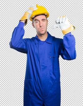 De ongerust gemaakte werkman met ontbreekt gebaar op witte achtergrond