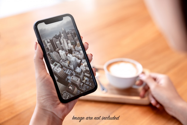 De spot omhoog van smartphone in vrouw dient koffiewinkel in