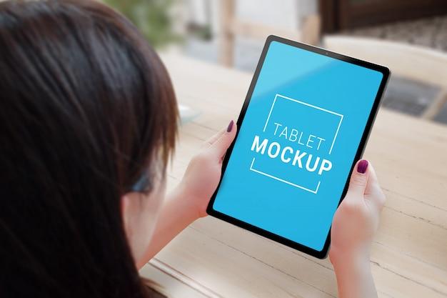 De tablet in vrouw overhandigt model op coffeeshopbureau.