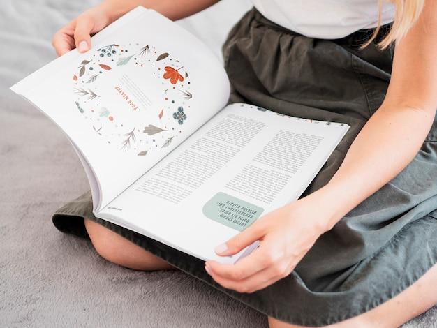 De vrouw die een tijdschrift op haar knieën houdt bespot omhoog