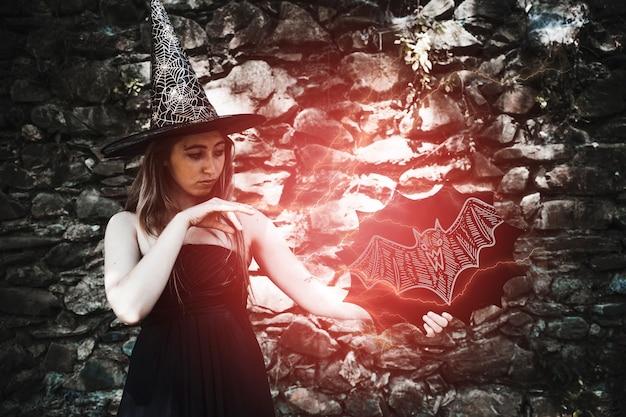 De vrouw kleedde zich als een heks die een rood lichtbetovering maakt