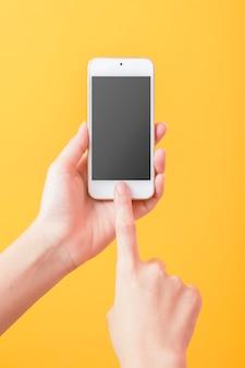 De vrouwenhand houdt slim telefoonmodel op gele achtergrond