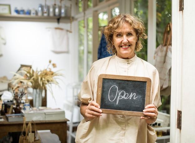 De winkeleigenaar die van de tuin een open teken houdt