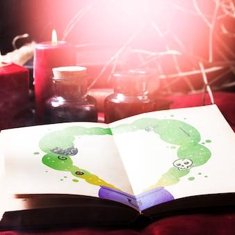 Decoración de escritorio de halloween y libro con dibujo de crisol