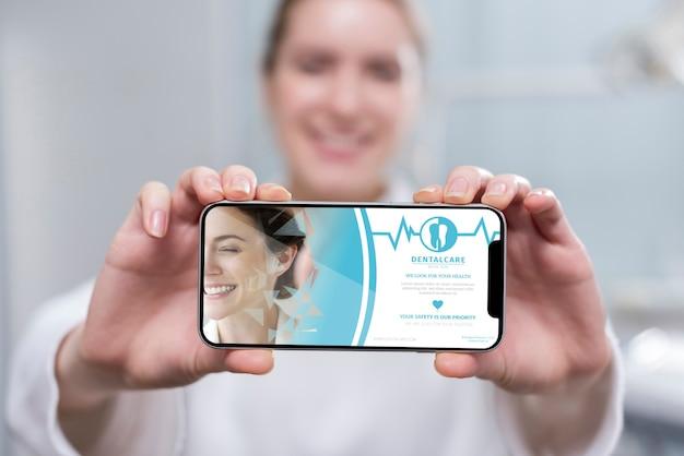 Dentista del primo piano che tiene uno smartphone