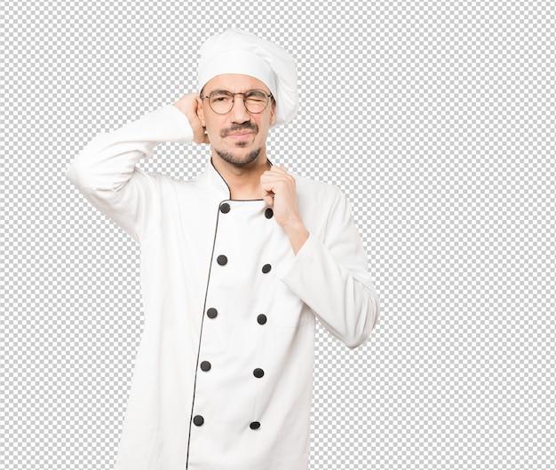 Depressieve jonge chef-kok doet een gebaar van stress