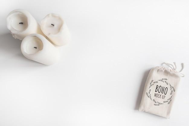 Derida su della borsa e delle candele di cotone della piattaforma di tarocchi su fondo bianco. progettazione di boho del sacchetto delle carte di tarocchi sulla tavola bianca con copyspace