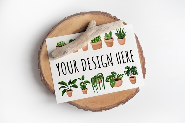Derida su della cartolina sulla sezione dell'albero di legno del taglio sulla tavola bianca. boho design di cartolina sul tavolo bianco