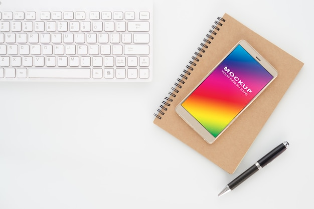 Derida sullo schermo in bianco dello smartphone sul taccuino con la tastiera di computer e della penna su bianco